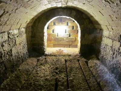 The inside of the firebox: upside-down railway irons used as firebars and the flue into the main chamber. This opening is 60cm x 60 cm. The perforated wall in the middle of the photo is the 'bag wall' which deflects the flame upwards so that the flames slowly move downwards through the kiln and are vented out at the bottom of the far side of the kiln.